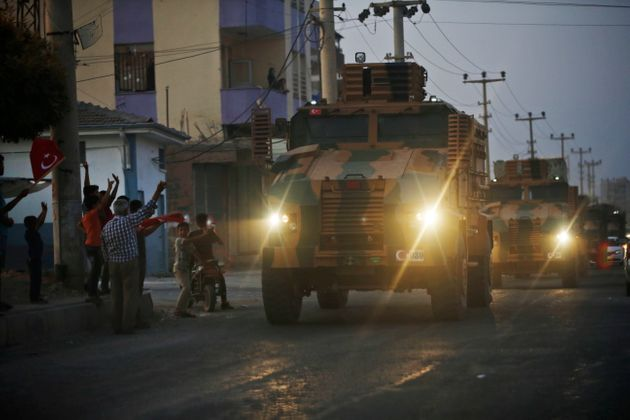 Local residents cheer and applaud as a convoy of Turkish forces vehicles is driven through the town of...