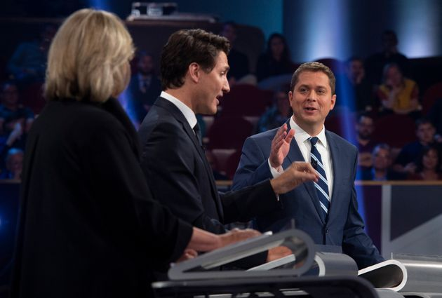 Green Party leader Elizabeth May looks on as Scheer and Trudeau debate a point during the federal leaders'...