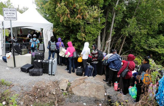 A line of asylum seekers who identified themselves as from Haiti wait to enter into Canada from Roxham...