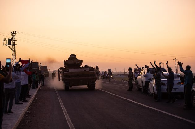 People wave as Turkish soldiers prepare to cross the border into Syria on Oct. 9, 2019 in Akcakale,