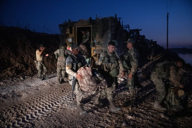 The first group of Turkish infantry prepare to enter Syria on the border between Turkey and Syria on...