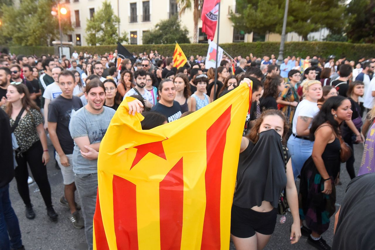 """A woman holds a Catalan pro-independence """"estelada"""" flag during a demonstration in Valencia on Oct. 9, 2019."""