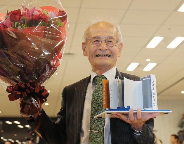 リチウムイオン電池の模型(右)と花束を手にする旭化成名誉フェローの吉野彰氏=9日、東京都千代田区