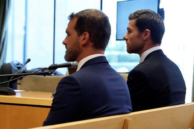 El exfutbolista Xabi Alonso (d), sentado en el banquillo de la puerta de Audiencia Provincial de