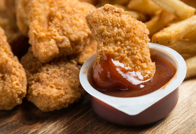 Chicken nuggets dipping in a BBQ sauce container and french