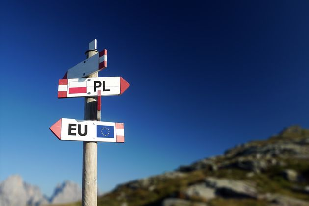 Poland and European Union flag in two directions on road sign. Diplomatic crisis