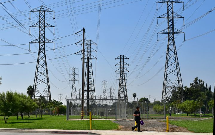 A pedestrian walks past a row of power lines in Rosemead, California, on October 9, as southern California braces for potenti