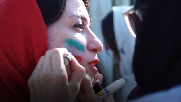 Des femmes se maquillent aux couleurs de l'Iran avant la rencontre Iran-Cambodge, jeudi 10