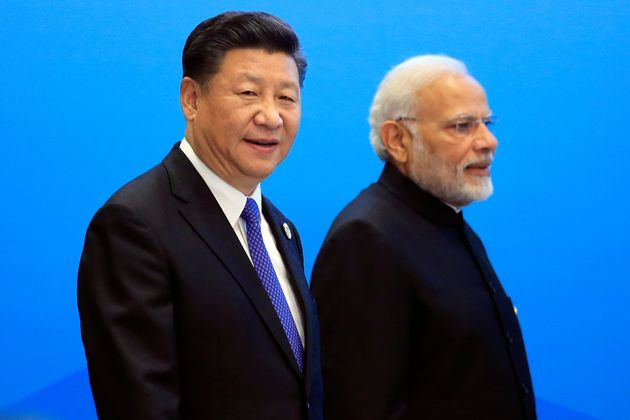China's President Xi Jinping and India's Prime Minister Narendra Modi arrive for a signing ceremony during...