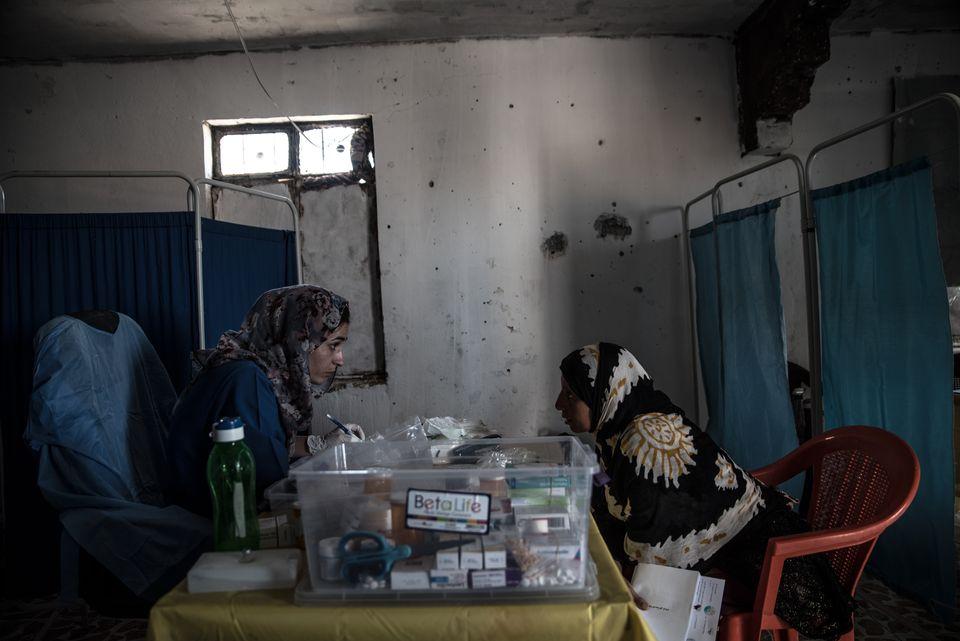 Una mujer habla con una enfermera en una consulta, en la villa árabe de Bir