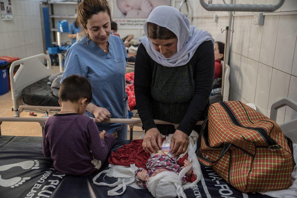 Una mujer yazidí atiende a un bebé, en presencia del personal