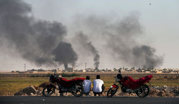 People in Akcakale Sanliurfa province, southeastern Turkey, at the border with Syria, watch smoke billowing...