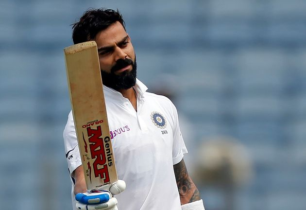 Indian cricketer Virat Kohli celebrates after scoring a century during the second day of the second cricket...