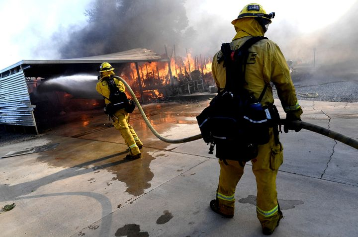 Firefighters try to protect surrounding homes as they battle the Sandalwood Fire in the Villa Calimesa Mobile Home Park in Ca