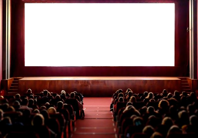 Cinema empty screen with audience. Blurred People silhouettes watching movie performance. Copy