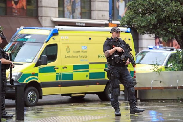 An armed police officer outside the Arndale Centre in Manchester where at least four people have been...