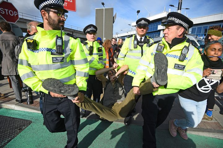 <strong>A man is removed by police officers after activists staged a 'Hong Kong style' blockage of the exit from the train station to City Airport, London</strong>