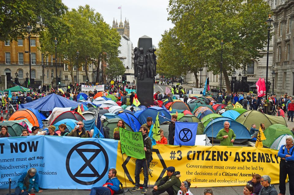 Extinction Rebellion (XR) protesters camp in tents around the Monument to the Women of World War II on...