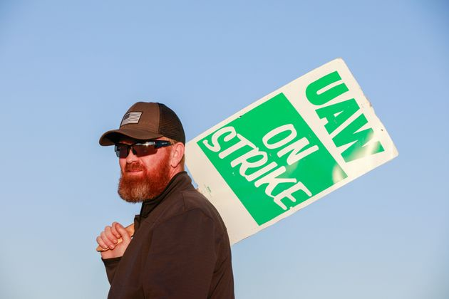 A member of UAW Local 440 on a General Motors picket line in Bedford, Indiana. The strike has cost GM...