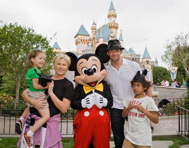 Jackman and his family pose with Mickey Mouse outside Sleeping Beauty Castle at Disneyland on April 23,...