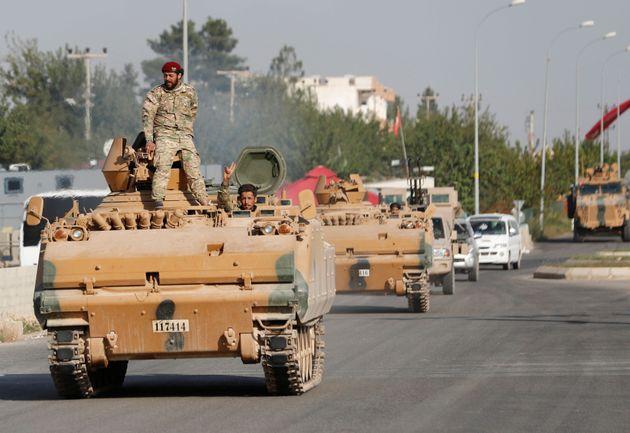 Αντάρτες του Συριακού Εθνικού Στρατού (πιο γνωστού ως Εθνικού Απελευθερωτικού Στρατου της Συρίας) στέκονται πάνω σε τουρκικό άρμα μάχης, στην επαρχία της Σανλιούρφα, στα σύνορα Τουρκίας - Συρίας. 11 Οκτωβρίου 2019.