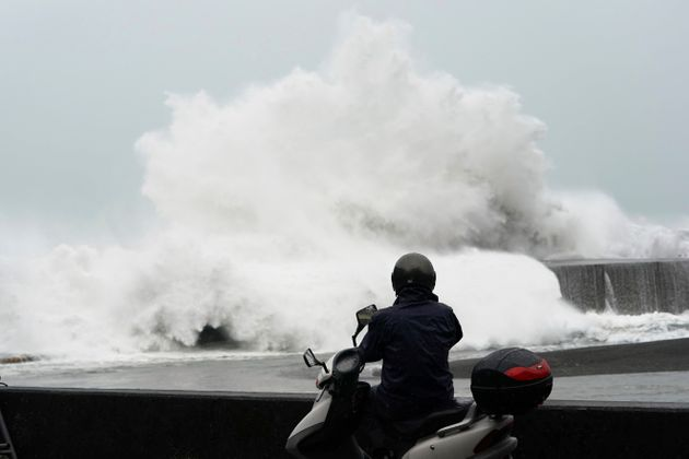 A man looks at surging waves hitting against the breakwater while Typhoon Hagibis approaches at a port...
