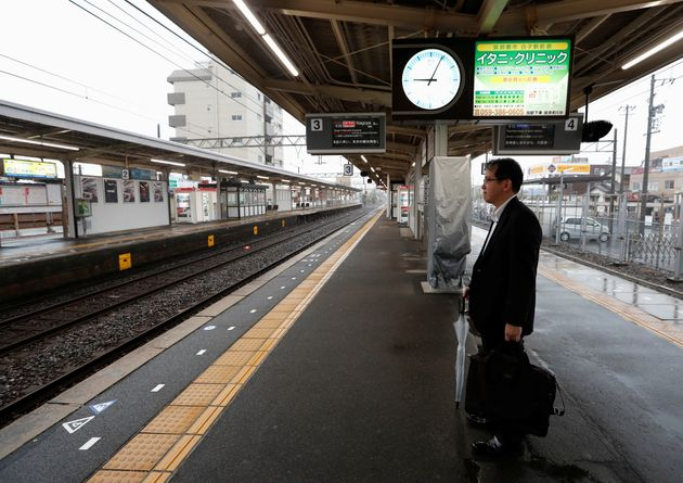 A man waits for a train at an almost empty Shiroko station, during heavy rain and winds ahead of Typhoon...