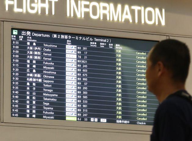 台風19号の影響で、欠航の表示が並ぶ羽田空港出発ロビーの電光掲示板=12日午前、東京都大田区