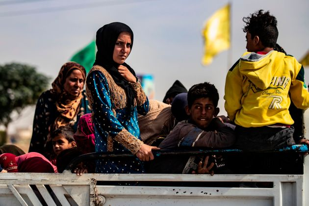 Displaced Syrians sit in the back of a pick up truck as Arab and Kurdish civilians flee amid Turkey's...