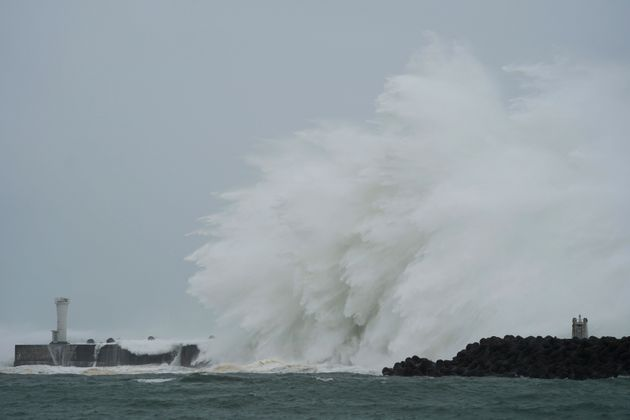Surging waves hit against the breakwater and a lighthouse as Typhoon Hagibis approaches at a port in...