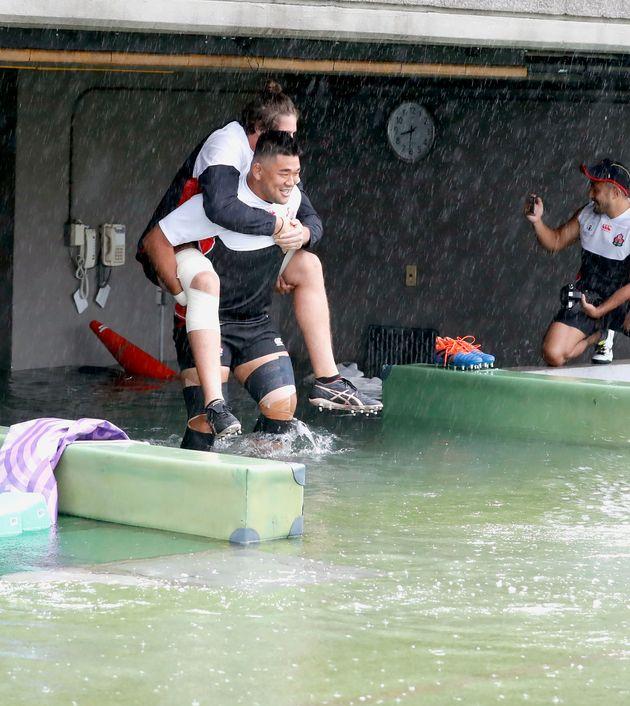 Japan's rugby team player Jiwon Koo, carries teammate James Moore in a flooded walkway at a stadium...