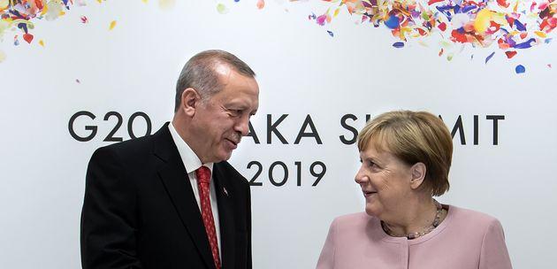 29 June 2019, Japan, Osaka: Federal Chancellor Angela Merkel (r, CDU) and Recep Tayyip Erdogan, President...