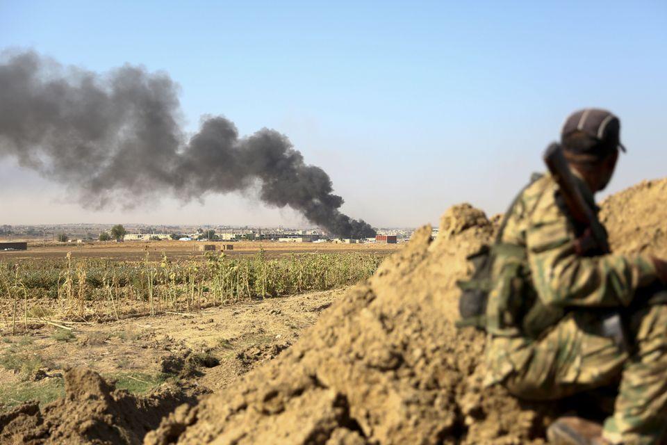 Σύροι αντάρτες κοντά στη Ρας Αλ Αΐν, καθώς ένα κτίριο έχει τυλιχθεί στις φλόγες.