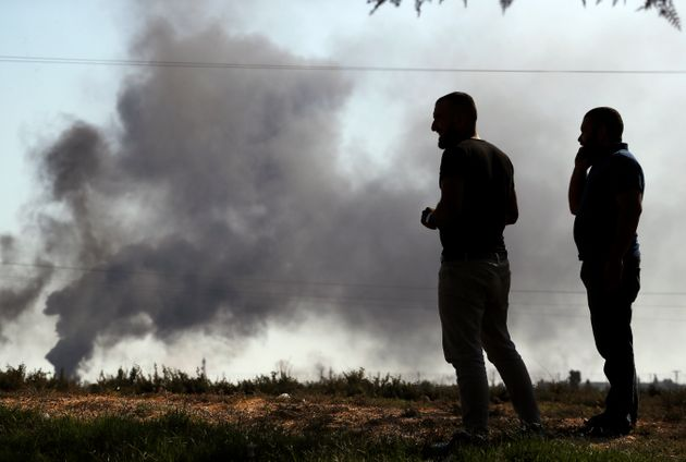 People in Akcakale ,Sanliurfa province, southeastern Turkey, at the border with Syria, watch smoke billowing...