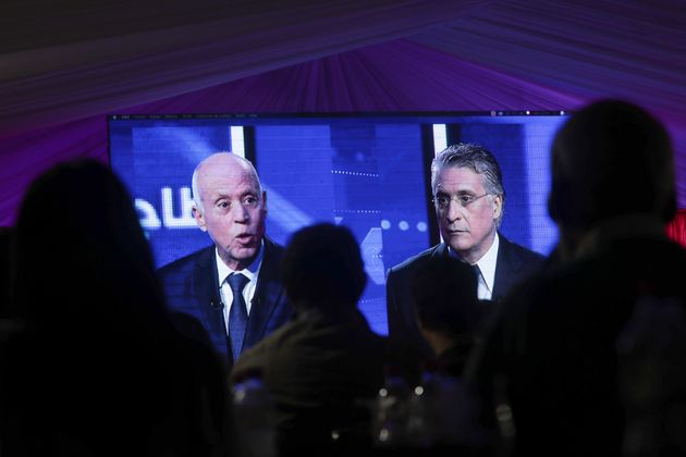 CORRECTS POSITION - People watch a televised debate between presidential candidates Kais Saied, left,...