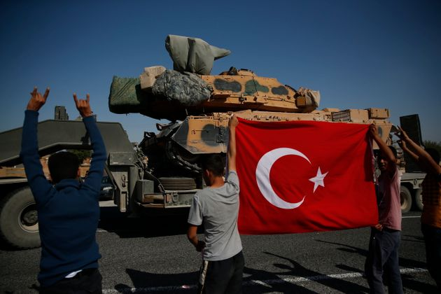 Local residents applaud as a convoy of Turkish forces trucks transporting tanks is driven in Sanliurfa...