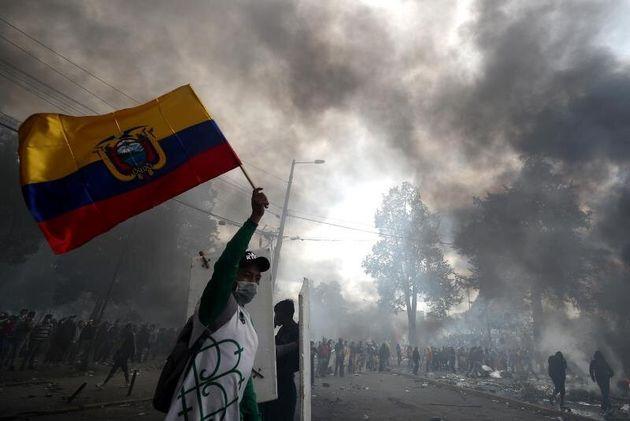 Un hombre ondea la bandera ecuatoriana mientras manifestantes se aproximan a la sede de la Contraloría...
