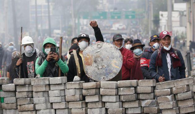 Des manifestants derrière des barricades lors d'affrontements avec la police à Quito, en...