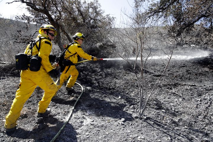 Brett Palmer, left, Anthony Ayala with the South Placer Fire Dept. hose down hot spot from a wildfire Saturday, Oct. 12, 2019