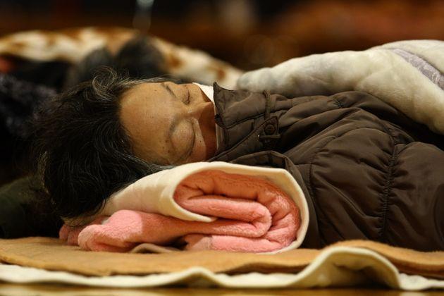 Une femme dort dans un refuge à Tokyo, ce 12