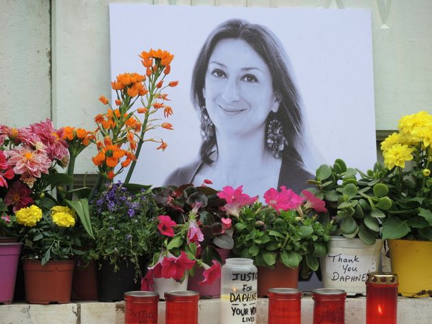 10 April 2018, Malta, Bidnija: At the feet of a memorial oposite the palace of justice are flowers and...