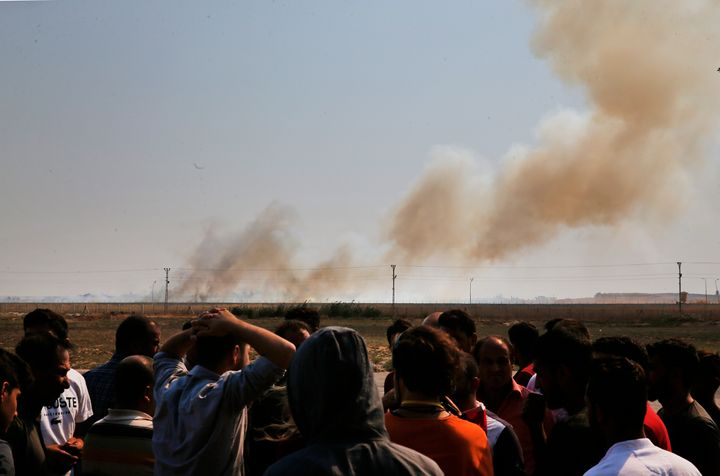 People watch from Akcakale, Sanliurfa province, southeastern Turkey, as smoke billows from fires on targets in Tel Abyad, Syr