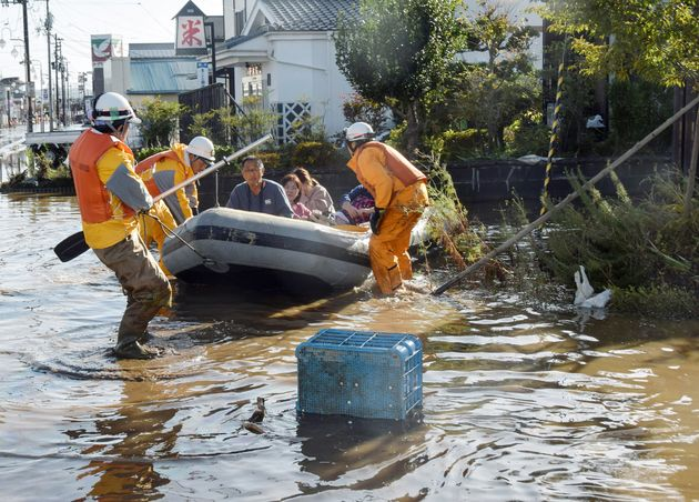 Fire department workers evacuate residents from a flooded area in Fukushima on Oct. 13, 2019, one day...