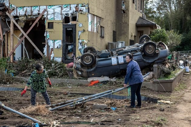 People recover items next to their house after it was damaged by a tornado shortly before the arrival...