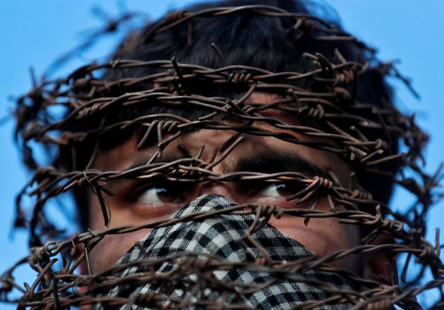 A masked Kashmiri man with his head covered with barbed wire attends a protest after Friday prayers during...