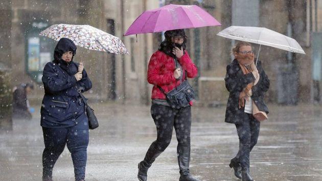 Varias personas transitan bajo la lluvia la plaza del Obradoiro, en Santiago de