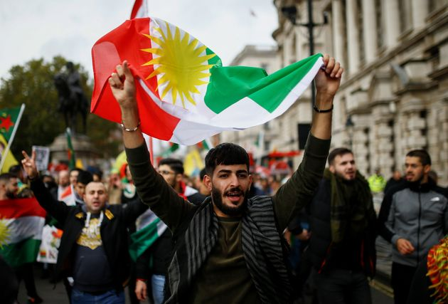 A man holds a flag during a pro-Kurdish rally against Turkey's military action in northeastern Syria,...