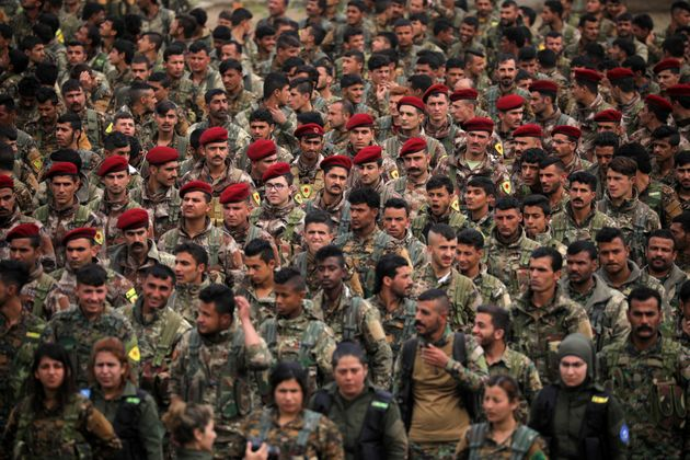 Kurdish fighters from the People's Protection Units (YPG) take part in a military parade as they celebrate...