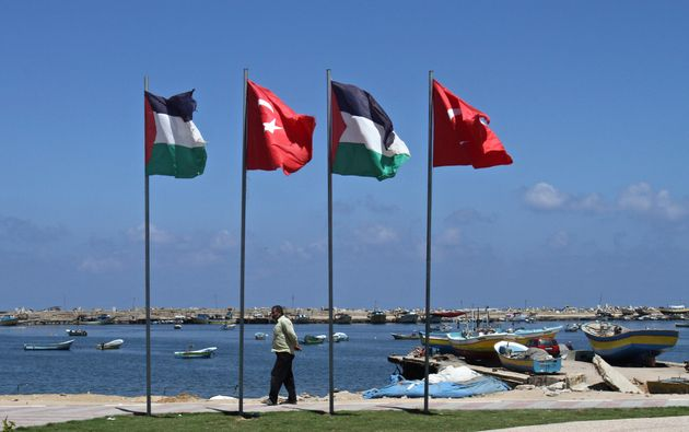 A Palestinian fisherman walks under Palestinian and Turkish flags at a memorial site in memory of nine...