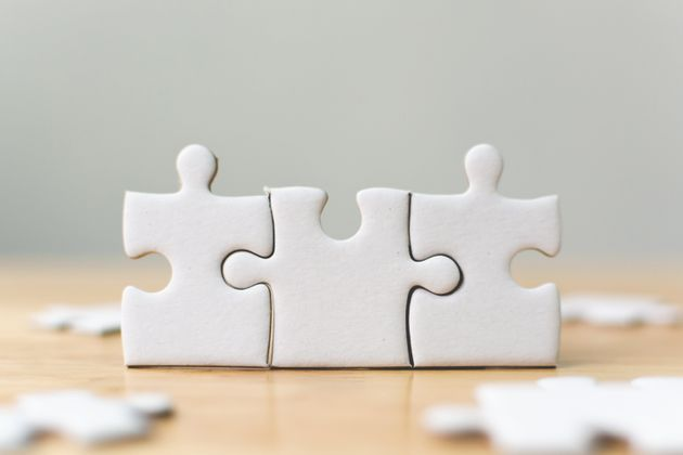 White jigsaw puzzle connecting together. Team business success partnership or teamwork